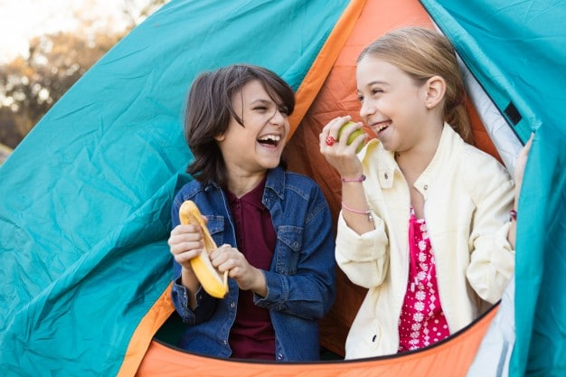 kids having a great time while eating on their camping activity