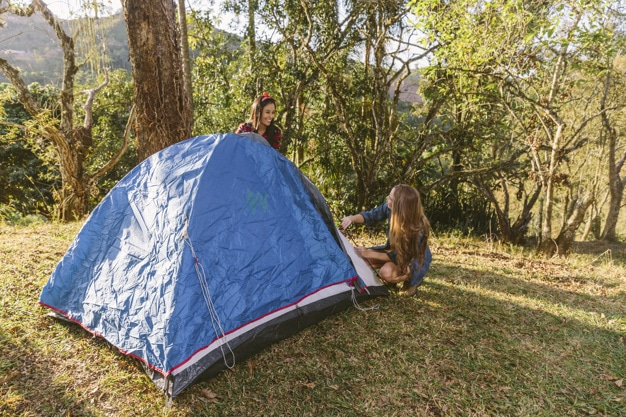 girls enjoy setting up their tent in the woods