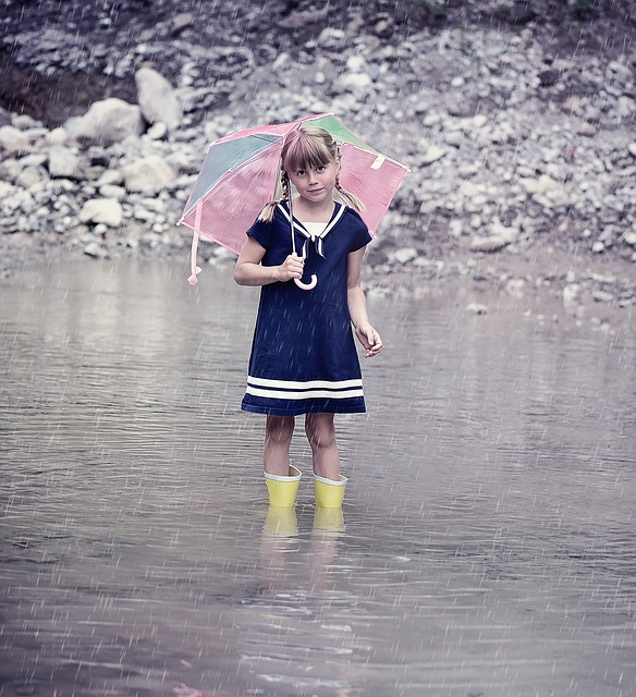 Girl in dress standing in a puddle of water