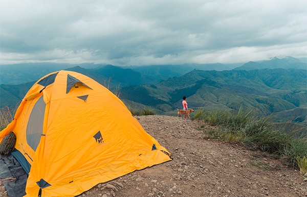 Woman and a dog is at the peak of the mountain and behind them is the best 4 season tent